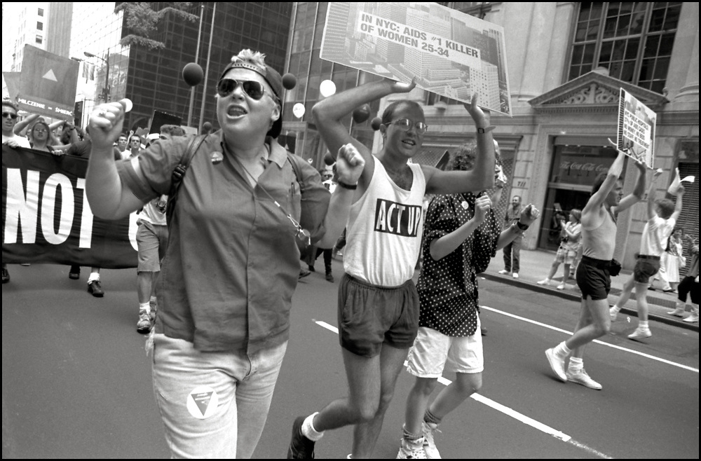 """Gerri Wells and Robert Hilferty of ACT UP NY, on June 24, 1989, the 20th anniversary of the Stonewall riots, participating in a renegade march up 6th avenue to Central Park. Themed, """"In The Tradition"""", this march followed the same route as the original march 20 years ago and was designed as a rebuke to the corporatization of the gay pride parade."""
