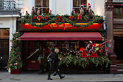 A man walking whilst looking at his mobile phone as he walks past Clos Maggiore resturant at Covent Garden on the 3rd December 2019 in London in the United Kingdom.