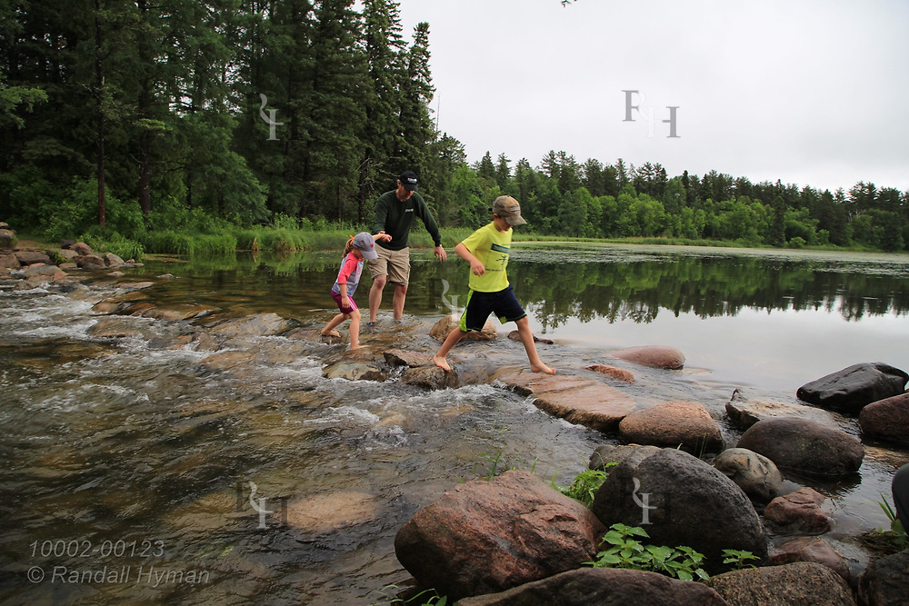 Father helps children walk across Lake Itasca outlet that forms the headwaters of the Mississippi River; Itasca State Park, Minnesota.