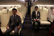 Two employees of the Japanese aircraft manufacturer Mitsubishi sit in a full-scale model of their MRJ at the Paris Air Show, Le Bourget France. Seated in different rows of this stylish small regional jet, they awkwardly stare expressionless, straight ahead and although the seats are real, the mock-up fuselage is in the middle of an exhibition hall. The MRJ is a next generation jetliner with 70 or 90 seat economy class configurations, the first regional jet to adopt composite materials for its wings and vertical fins on significant scale. The Paris Air Show expo is a commercial air show, organised by the French aerospace industry who demonstrate military and civilian aircraft equipment to interested customers.