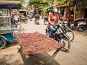 24 FEBRUARY 2015 - PHNOM PENH, CAMBODIA: A man rides his motorcycle past of rack of meat drying in the sun in front of the White Building in Phnom Penh. The White Building, the first modern apartment building in Phnom Penh, originally had 468 apartments, and was opened the early 1960s. The project was overseen by Vann Molyvann, the first Cambodian architect educated in France. The building was abandoned during the Khmer Rouge occupation. After the Khmer Rouge were expelled from Phnom Penh in 1979, artists and dancers moved into the White Building. Now about 2,500 people, mostly urban and working poor, live in the building. Ownership of the building is in dispute. No single entity owns the building, some units are owned by their occupants, others units are owned by companies who lease out apartments. Many of the original apartments have been subdivided since the building opened and serve as homes to two or three families. The building has not been renovated since the early 1970s and is in disrepair. Phnom Penh officials have tried to evict the tenants and demolish the building but residents refuse to move out.  PHOTO BY JACK KURTZ