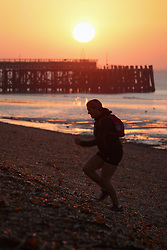 © Licensed to London News Pictures. 01/10/2015. Southsea, Hampshire, UK. A woman training during sunrise on Southsea beach in Portsmouth this morning, 1st October 2015, on what is set to be another dry and fine day in the south of England. Photo credit : Rob Arnold/LNP