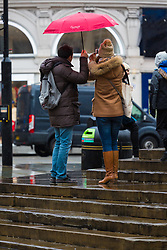 Two tourists share an umbrella in Piccadilly Circus. As forecasters predicted, the rain arrives in London where Londoners and tourists go about their business. London, February 13 2018.