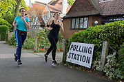 Before voting for the European Elections commences at 7am, local runners jog past the entrance of the Polling Station at St. Barnabas Parish Hall in Dulwich Village, on 23rd May 2019, in south London, England UK.