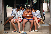 On a slow Saturday in Ban Muang Wa village, outside Chiang Mai, Thailand, the hottest action in the village is in the cool shade under the Khuenkaew's house. Three weeks ago, Boontham and Bourphet gave their son Visith, 9, a hand-held video game, and the household has been filled with its beeps and buzzes ever since. Here his best friend plays with the game as Visith's 14-year-old sister Jeeraporn, left, and her friends watch. Published in Material World page 82. The Khuenkaew family lives in a wooden 728-square-foot house on stilts, surrounded by rice fields in the Ban Muang Wa village, outside the northern town of Chiang Mai, in Thailand.