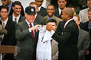 President Bill Clinton, wearing a New York Yankees baseball cap accepts a NY Yankees jersey from pitcher Orlando Hernandez as the 1998 World Series winning Yankees visited the White House June 10, 1999 in Washington, DC.