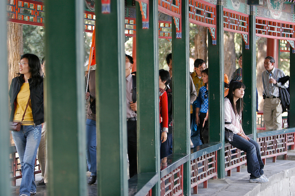 A visitor rests along an outdoor walkway inside the Summer Palace.  The Summer Palace in north west Beijing, China was built in the Jin Dynasty.  The Summer Palace is over 700 acres, 3/4 of which is the Kunming Lake.