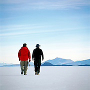Rearview of two men walking on Salar de Uyuni salt flats, Potosi Region, Bolivia. The Salar de Uyuni are the worlds largest salt flats.
