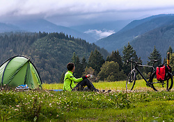 Man at his campsite looking at mountains