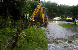 Memories return of June 2007 as heavy rains cause more flooding in Sheffield. Two houses on Ecclesfield Common are threatened by flood waters from over-flowing streams as police officers who have been battling against the flood waters with buckets and hand shovels get reinforcements in the shape of a JCB mechanical digger 09 June 2009 Copyright Paul David Drabble