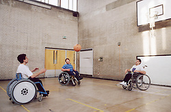 Group of men with disabilities; who are wheelchair users; playing game of basketball in sports hall,