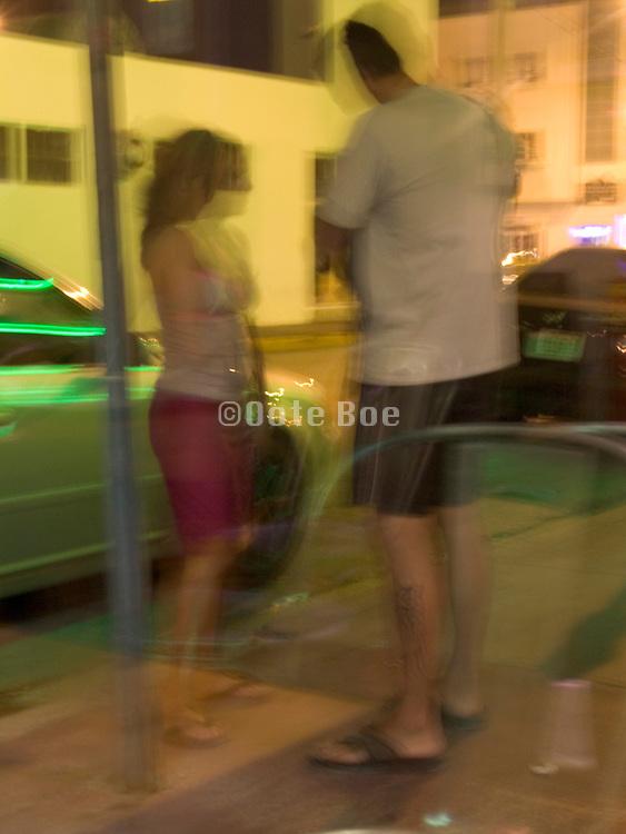 Couple standing on sidewalk at night