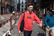 Young man wearing a red sweatshirt with the word Dad printed on it in London, United Kingdom. One can imagine this is a piece of ironic fashion in hipster London.