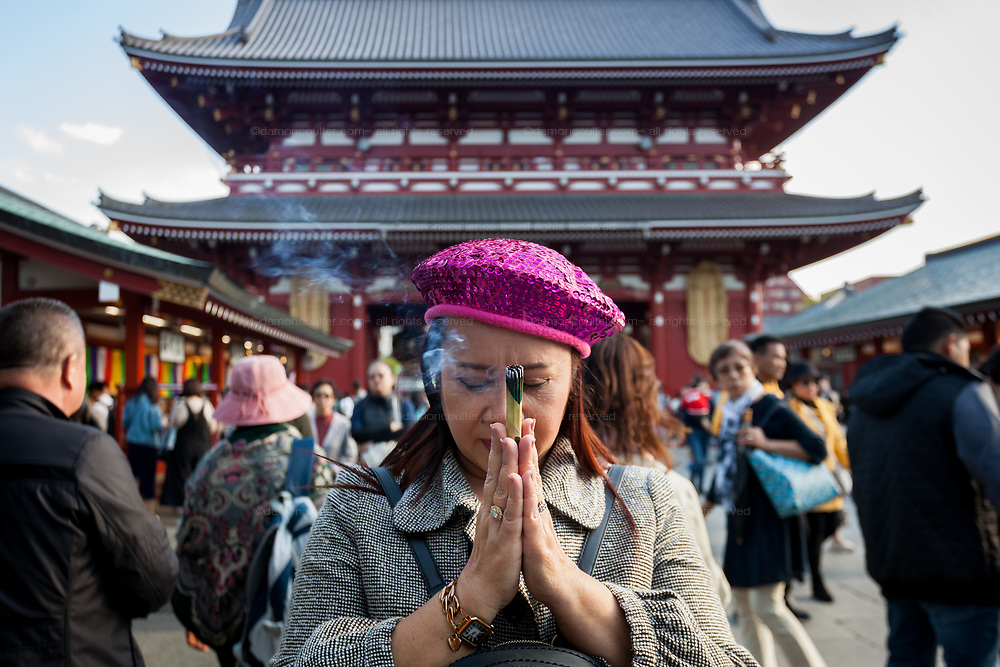 A female tourist from Thailand prays with an incense stick at Senso-Ji temple in Asakusa, Tokyo, Japan. Monday April 15th 2019