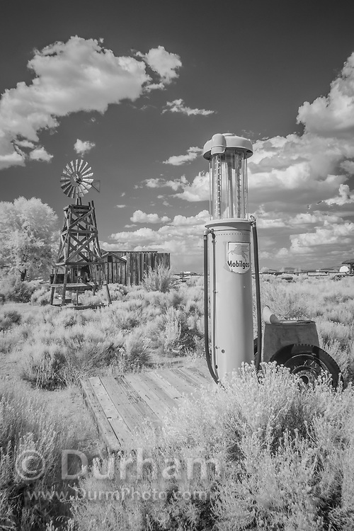 Fort Rock homestead with windmill water pump and vintage gas pump. In 1988 the Fort Rock Valley Historical Society opened the Fort Rock Homestead Village Museum which preserves and protects homestead-era structures. The buildings were moved from their original locations to the museum site just west of the town of Fort Rock., Oregon. © Michael Durham