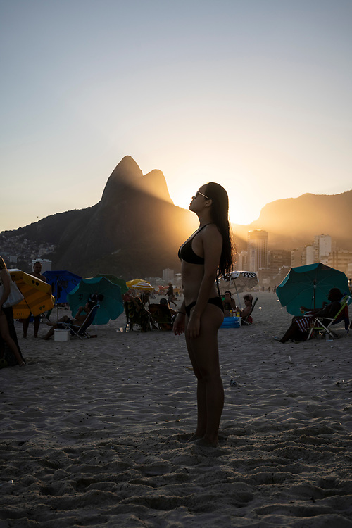 Rio de Janeiro, Brazil - March 9, 2019: An American traveling in Brazil stands on Ipanema Beach at sunset in Rio de Janeiro, Brazil.