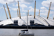 A yacht on the river Thames passes the O2 Arena formerly the Millennium Dome on the Greenwich Peninsula, beneath a blue sky and clouds, on 11th August 2021, in London, England. The O2 is a music, sport and entertainment venue, opened in the year 2000.