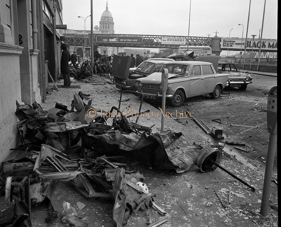 Car Bomb Damage in Dublin (E10)..1972.02.12.1972..12.02.1972..2nd December 1972..On the morning of 2nd December '72 two car bombs exploded in Dublin City. At Sackville Place two busmen were killed as they waited in their car to resume work. The busmen were named as George Bradshaw (30) and Thomas Duffy (23). The bomb was thought to be planted by a Northern Ireland subversive group who hoped to influence legislation going through Dail Eireann in relation to the I.R.A...Image of part of the car,thought to be the bomb vehicle, tossed against the wall along Eden Quay.