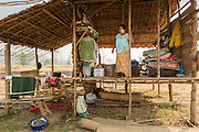 """01 MARCH 2014 - MAE SOT, TAK, THAILAND: A Burmese woman waits for her husband to bring supplies for a new exterior wall on their home in a small Burmese community in the forest a few kilometers north of Mae Sot. The new wall is a rattan mat. Mae Sot, on the Thai-Myanmer (Burma) border, has a very large population of Burmese migrants. Some are refugees who left Myanmar to escape civil unrest and political persecution, others are """"economic refugees"""" who came to Thailand looking for work and better opportunities.    PHOTO BY JACK KURTZ"""