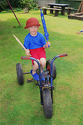 Young boy with autism sitting on tricycle in garden,