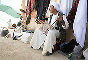 Israel, Negev Desert, Bedouin man playing music on a Rebab