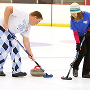 Patrick Rameas, left and Maggie Schaber sweep a stone during a curling match at the Wilmington Ice House. (Jason A. Frizzelle)