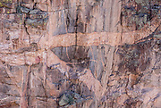 See pegmatite intrusions from Rock Point, in Black Canyon of the Gunnison National Park, near Montrose, Colorado, USA. Pressurized molten rock was forced into 1.7-billion-year-old metamorphic rock, forming pink pegmatite stripes on Colorado's highest cliffs. With two million years to work, the Gunnison River and weathering have sculpted a vertical wilderness of rock, water, and sky.