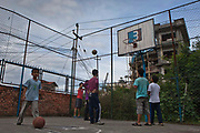 Nepalese boys playing basketball outside of their care home in Kathmandu, Nepal.  The care home is run by the Friends of Needy Children organization.  It provides a loving home for boys and girls who are orphaned or abandoned.  Abject poverty, domestic violence and armed conflict have caused many Nepalese children orphaned and homeless.