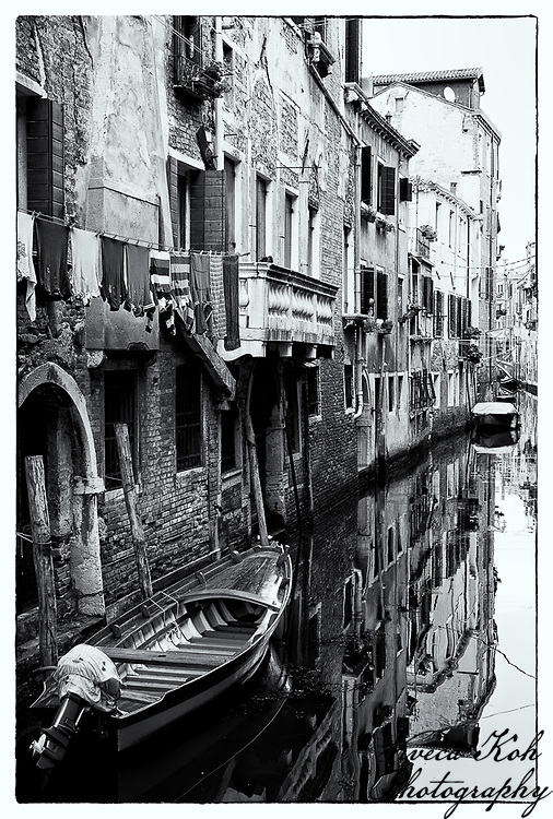 Old buildings and a boat in Venice, Italy, reflected in the canal below.