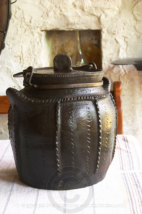 Traditional black earthenware pot with lid and handle and decoration called cereme used for cooking food. The black colour comes from the production process. Tradita traditional restaurant, Shkodra. Albania, Balkan, Europe.