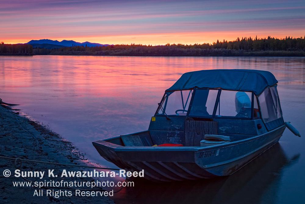 Flat bottom river boats moored at the shore of Kuskokwim River. Pastel sunset reflects on the river. McGrath, Interior Alaska, Autumn.