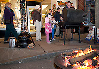 "Randy Bullerwell of Of My Life Jewelers treats Lila Miller, Katie Miller, Joshua Thomas, Elijah Miller and Jenn Miller to roasted chestnuts Friday evening during the ""Christmas in the Village"" festivities in downtown Laconia.  (Karen Bobotas/for the Laconia Daily Sun)"