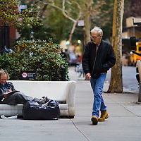 A homeless man sits and reads a newspaper from a sofa thrown out on the street in midtown manhattan new york city