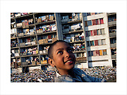A child plays at the infamous Lunik IX housing estate which has become a Roma ghetto. The municipality refuses to collect the rubbish. It used to be a military barracks but was 'given' to the Roma after the velvet revolution. Kosice, Slovakia 2003. ..Roma Gypsies left Rajasthan in India a thousand years ago, in the ninth and tenth centuries. They were pushed west by the Ottoman Muslim Empire as it moved through Persia towards the frontiers of Europe. They entered Europe in the foutrteenth century and were slaves in Romania and Moldavia until the mid 1850s. There are about 15 million Roma gypries in the world, about 12 million who live in Europe. they are Europe's largest ethnic minority. They have rich traditions and culture, their own language. They are renowned for their prowess in music and dance; they are also skilled craftsman, metal roofmakers, silver and goldsmiths. Their traveling and nomadic lifestyle which grew from a necessity to find work, and because they were often moved on from one place to the next, has given them both a liberty but also marks them as different and they are often feared by sedentary peoples, who label and scapegoat them. They are hardy survivors and live in the brunt of racism and prejudice, often marginalised, living in poverty, without proper human rights afforded to them..