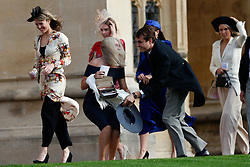 A guest stoops to collect her hat that blew off in the wind as she arrives for the wedding of Princess Eugenie to Jack Brooksbank at St George's Chapel in Windsor Castle.