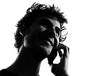 young man looking up telephone smiling portrait silhouette in studio isolated on white background