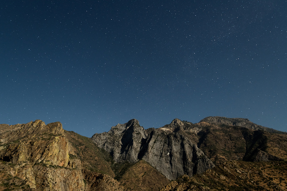 Stars shine above the walls of Kings Canyon in Kings Canyon National Park, California.