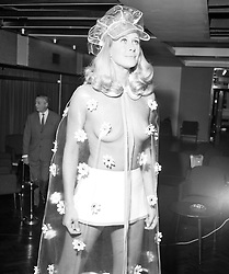 Aldine Honey models a Berkertex flower-patterned plastic rain cape worn over a mini skirt at a show of Spring fashions in London.