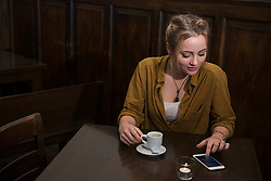 Young woman holding coffee cup and using mobile phone at restaurant