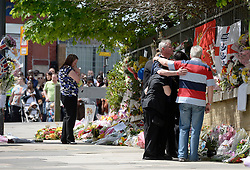 © London News Pictures. 26/05/2013. Woolwich, UK.  Family of murdered serviceman Drummer Lee Rigby embrace each other at the location of his death during a visit the scene of his death in Woolwick, London. Rebecca Rigby (left), wife of Drummer Lee Rigby  is pictured left holding a pink toy shaped like a pig. Drummer Lee Rigby was murdered by two men in Woolwich town centre in what is being described as a terrorist attack. Photo credit: Ben Cawthra/LNP