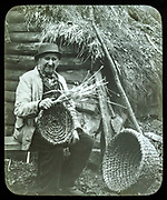 Portrait of elderly countryman weaving straw baskets in England, c 1890s-1900