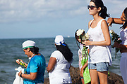 Brazilian women making offerings of flowers to the sea in honour of Yemanja. February 2nd is the feast of Yemanja, a Candomble Umbanda religious celebration, where thousands of adherants visit the Rio Vermehlo Red River to pay their respects to Yemanja, the Orixa goddess of the Sea and water.
