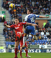 Photo: Paul Greenwood.<br />Wigan Athletic v Liverpool. The Barclays Premiership. 02/12/2006. Wigan's Lee McCullcoh, right, challenges Liverpool's Steve Finnan in the air.