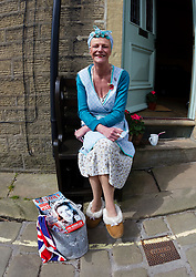 © Paul Thompson licensed to London News Pictures. 16/05/2015. Haworth, West Yorkshire, UK. A woman dresses as a housewife at Haworth 1940s weekend, an annual event in which people dress in period costume and visit the village of Haworth to relive the 1940s. Photo credit : Paul Thompson/LNP