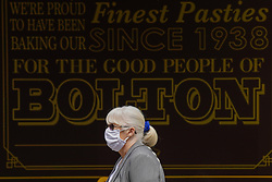 © Licensed to London News Pictures. 29/05/2021. Bolton,UK .A woman wears a face mask walks in Bolton town centre.. Bolton has the highest Covid-19 infection rate in the country as the Indian variant of Covid-19 continues to spread.  Photo credit: Ioannis Alexopoulos/LNP