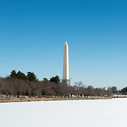 The Washington Monument towers above a frozen Tidal Basin covered in snow. Winter temperatures have been lower than average for the region.