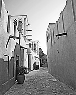 A black and white image of Traditional Middle Eastern Street in Dubai. This is part of the cultural centre in Dubai, an area preserved by the Shake and government of Dubai in order to get a flavour of how life was once lived in the city before the skyscrapers came. We see a traditional street with the high walled houses and cooling towers once common place in the city.