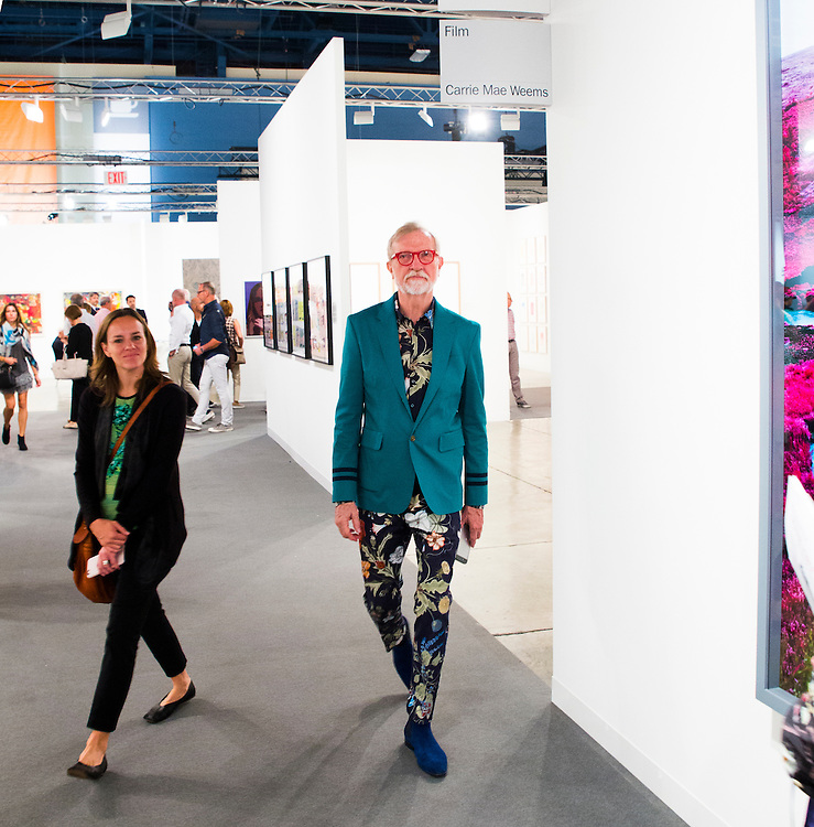 Guy in flowered shirt and pants, green jacket and red eyeglasses at Art Basel Miami Beach