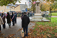 Man coming on his way back from shopping stops by the memorial on Remembrance day, Saint-Rémy-lès-Chevreuse. 11th November 2017.