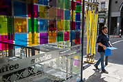 A male pedestrian carries a blue admin folder past the coloured squares of the Wrap It Up takeaway restarant on Fleet Street in the City of London, in the capital's financial district, at a time when workers are still largely working from home during the Coronavirus pandemic, on 1st September 2020, in London, England.